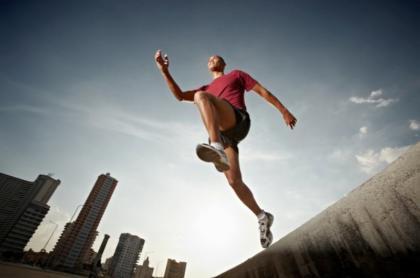 Фото спортсмена в прыжке на фоне города