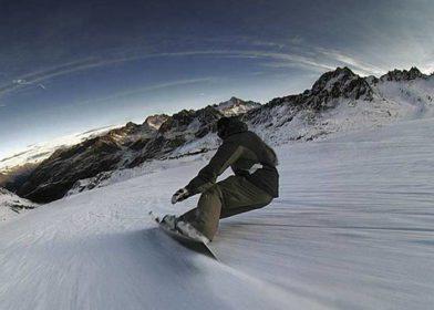 Райдер совершает скоростной спуск с горы на сноуборде